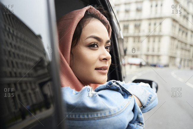 UK- England- London- young woman wearing hijab looking out of a taxi