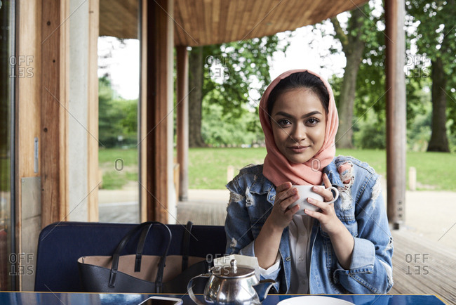 Young woman wearing hijab holding a cup on a terrace of a cafe
