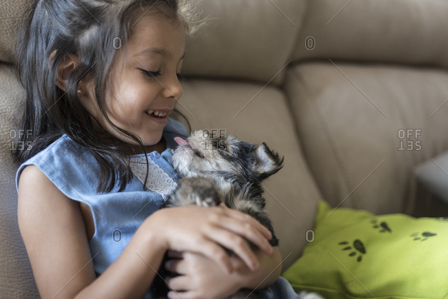 Happy Little Girl Sitting On The Couch With Puppy On Her Lap Stock
