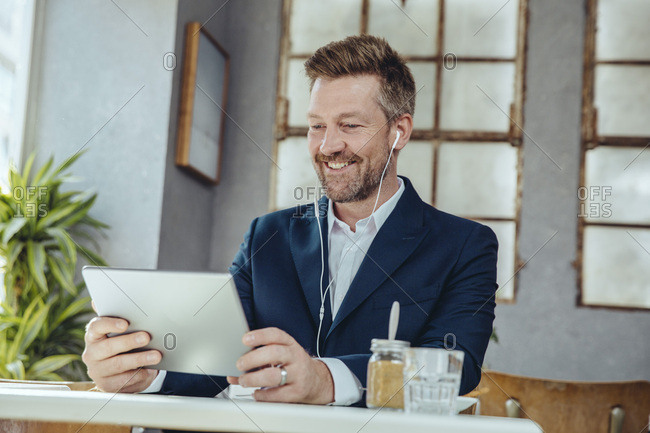 Smiling businessman with tablet and earbuds in a cafe