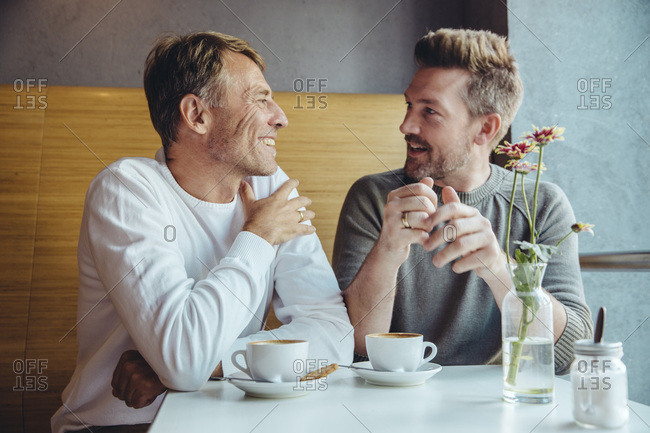 Gay couple talking in cafe