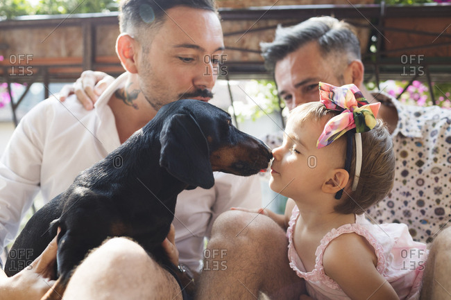 Gay couple with daughter and dog on balcony