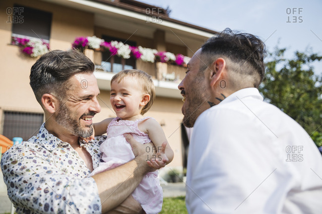 Happy gay couple with their child in the garden