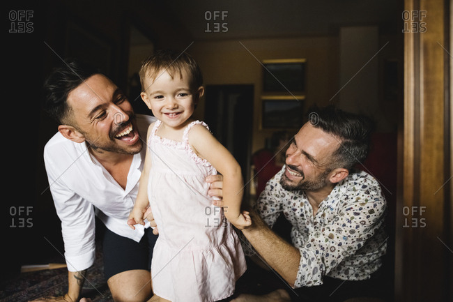 Happy gay couple playing with their little daughter at home