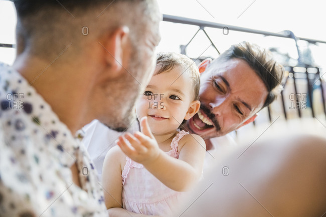 Happy gay couple with daughter on balcony