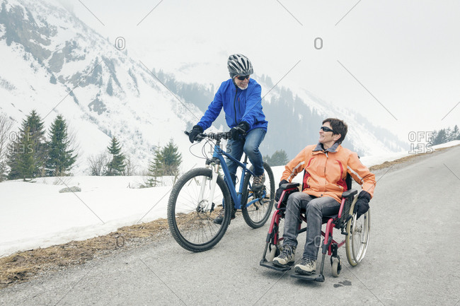 Austria- Damuels- senior couple with bike and wheelchair enjoying a winter day