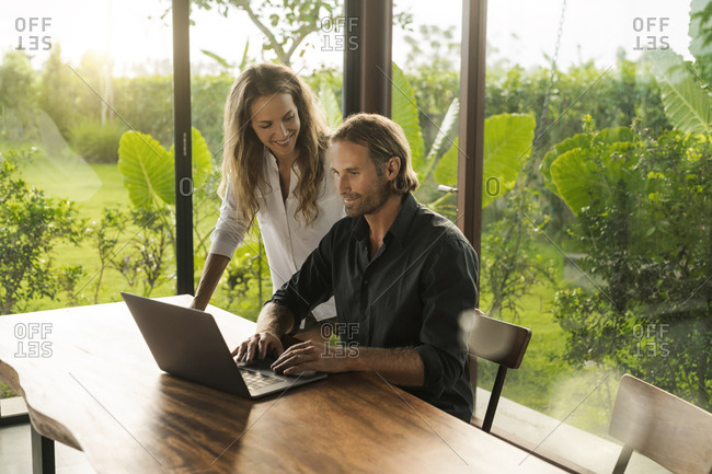 Woman smiling at husband working on laptop in design house surrounded by lush tropical garden