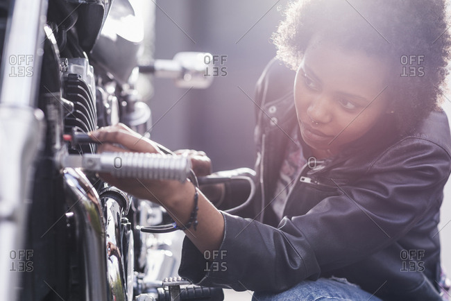 Young woman maintaining her motorcycle