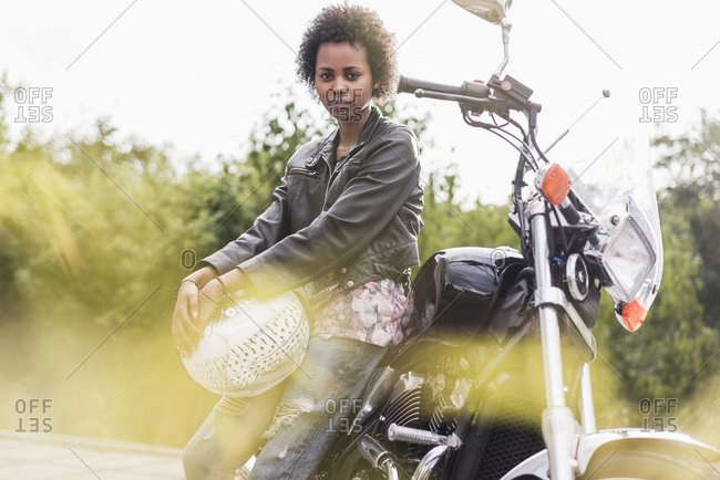 Portrait of young woman with her motorcycle