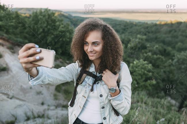 Smiling teenage girl taking selfie in nature