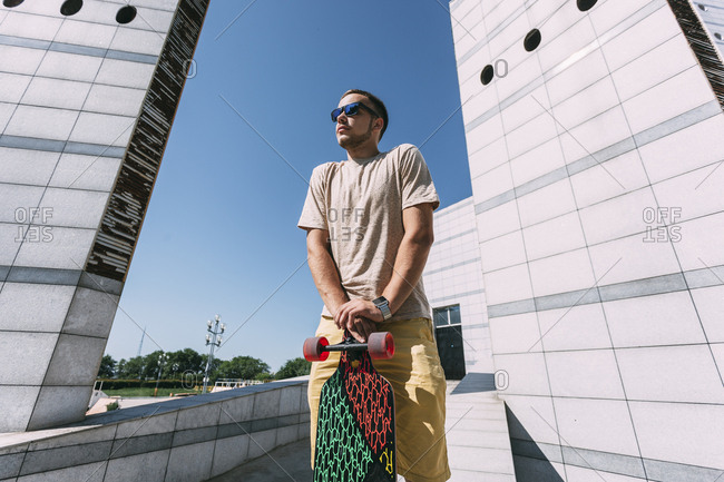 Young man with longboard surrounded by modern architecture