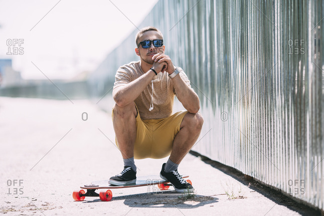 Young man crouching on longboard