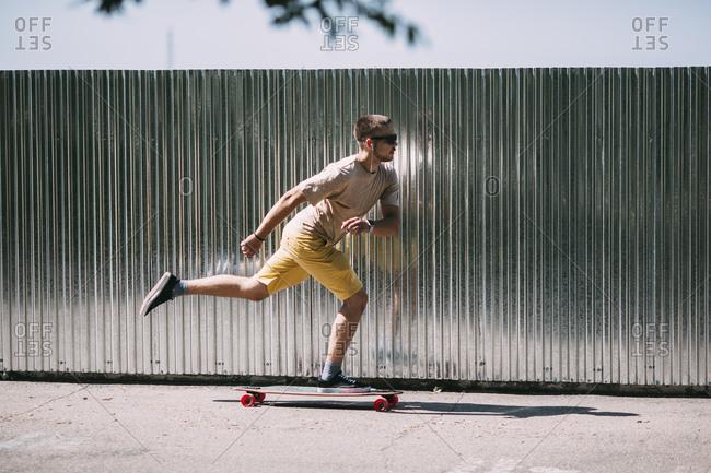 Young man riding skateboard along a wall