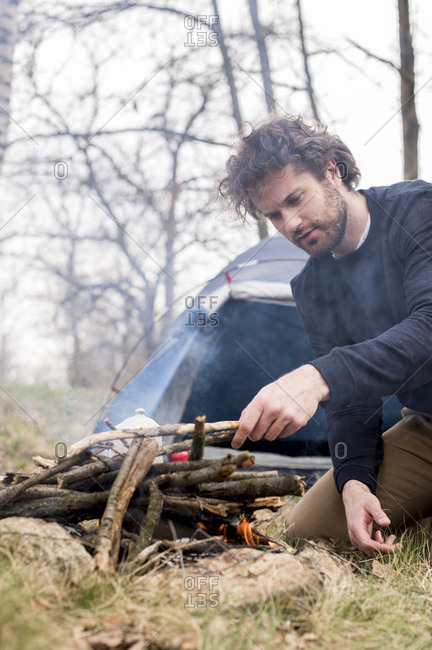 Man camping in forest preparing campfire