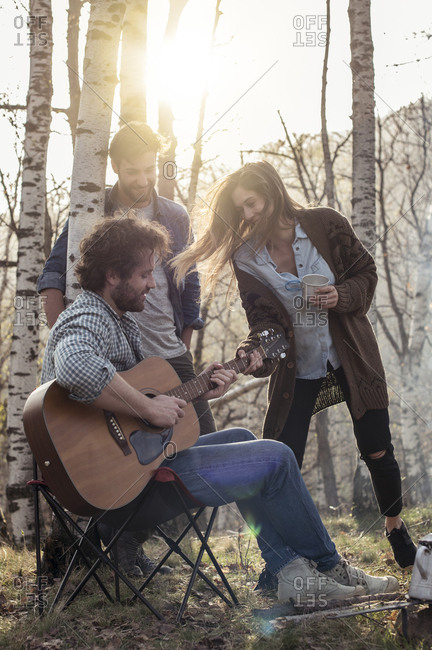 Friends in forest with man playing guitar
