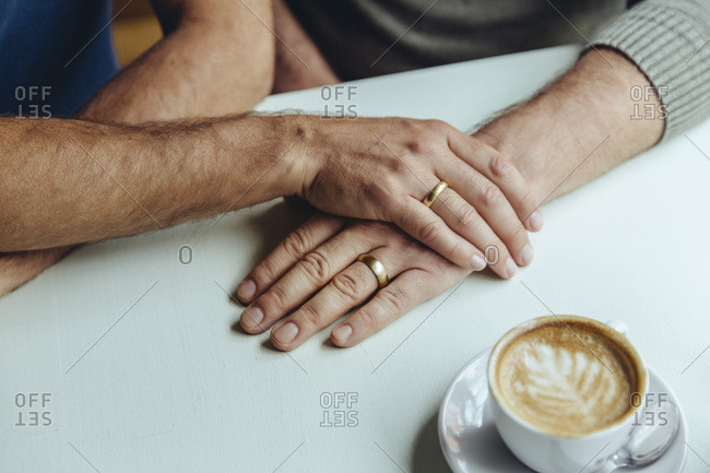 Close-up of men's hands with wedding rings and a cup of coffee