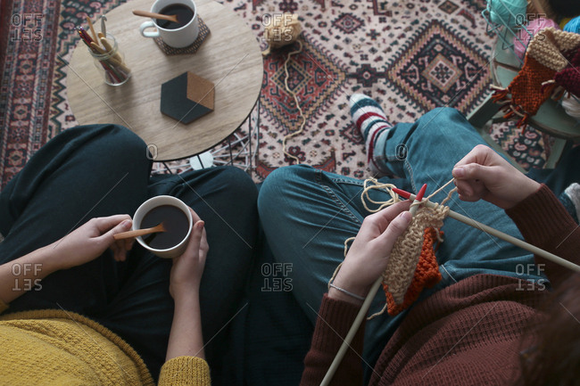 Young couple knitting and having cup  of coffee in living room- top view