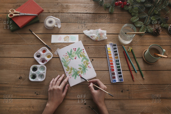 Young woman painting Christmas card with water colors- top view