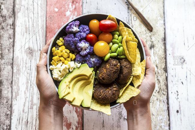 Girl's hands holding Quinoa veggie bowl of vegetables- feta- nachos and quinoa fritters