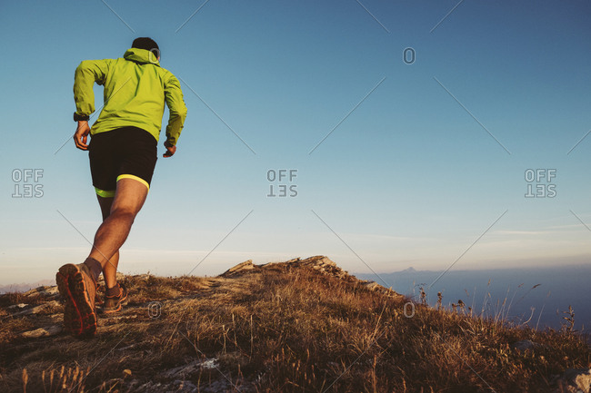 Italy- man running on mountain trail