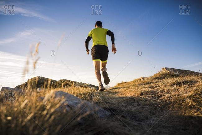 Italy- man running on mountain trail