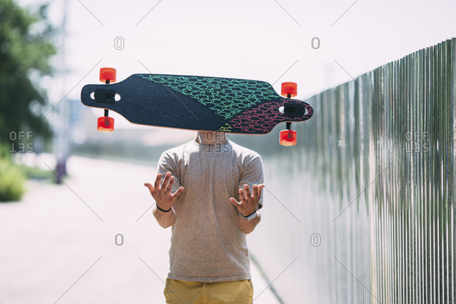 Obscured young man throwing longboard in the air
