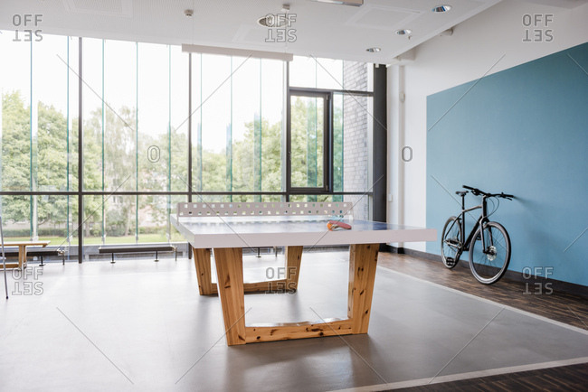 Table tennis table and bicycle in break room of modern office