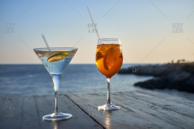 Glass of ice-cooled Spritz with orange slice and glass of Martini with lime slice in front of the sea