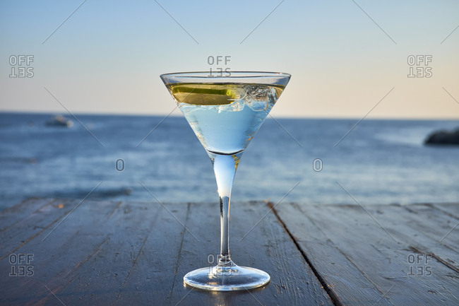 Glass of ice-cooled Martini with lime slice in front of the sea