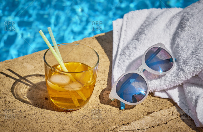 Glass of Crodino- sunglasses and towel at the poolside