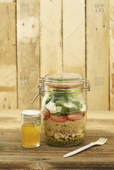 Preserving jar of mixed salad with peas- tuna- couscous- tomatoes- tuna- feta and jar of vinaigrette dressing