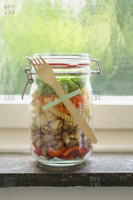 Preserving jar of vegan mixed salad with tofu and pasta on window sill