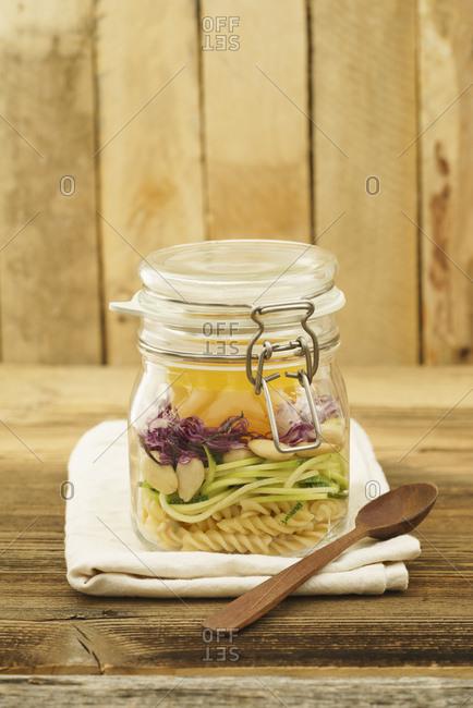 Preserving jar of vegan mixed salad with pasta