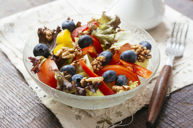 Glass bowl of mixed salad with different raw vegetables- blueberries and walnuts