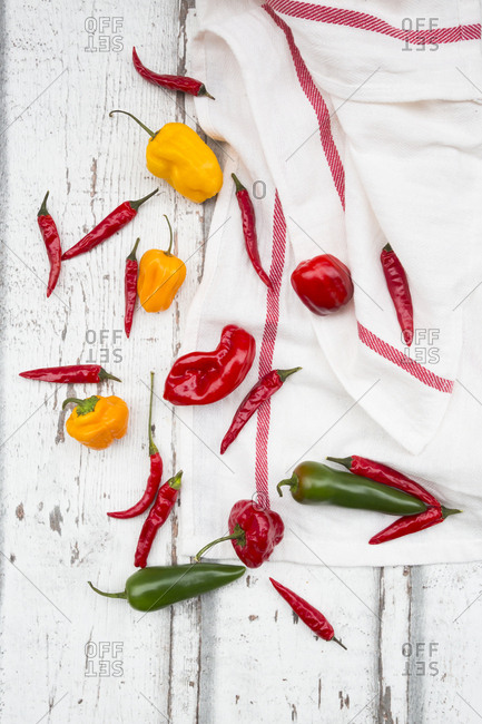 Various chili pods on kitchen towel and wood