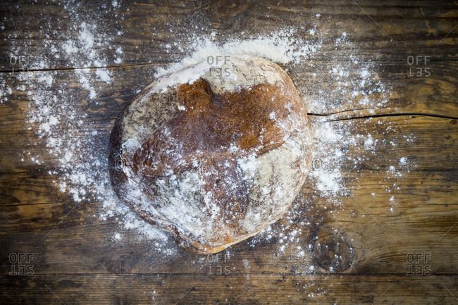 Wheat bread powdered with flour on dark wood