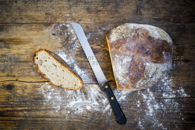 Cut wheat bread powdered with flour and bread knife on dark wood