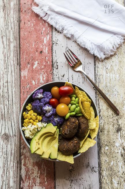 Quinoa veggie bowl of avocado- Edamame- tomatoes- corn- feta- nachos- cauliflower and quinoa fritters