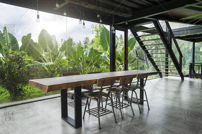 Modern wooden table in contemporary design house with glass facade surrounded by lush tropical garden