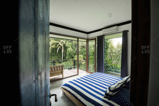 Modern cozy bedroom in contemporary design house with glass facade surrounded by lush tropical garden