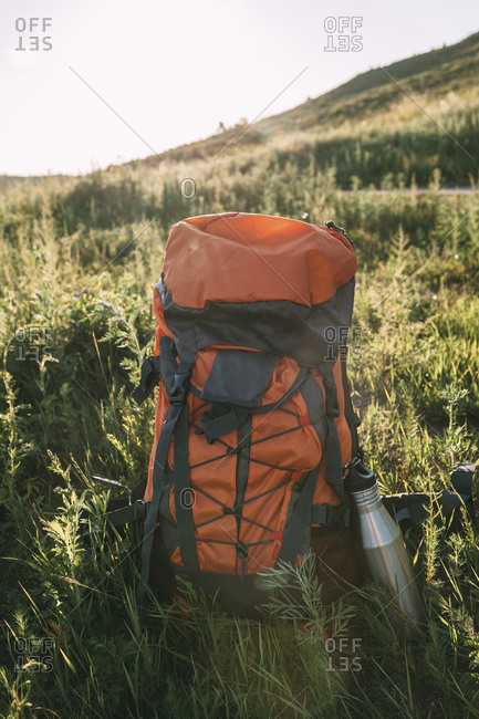 Backpack and thermos flask on a meadow