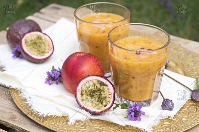 Two glasses of fruit smoothie with passion fruit- nectarine- pomegranate juice and rice milk
