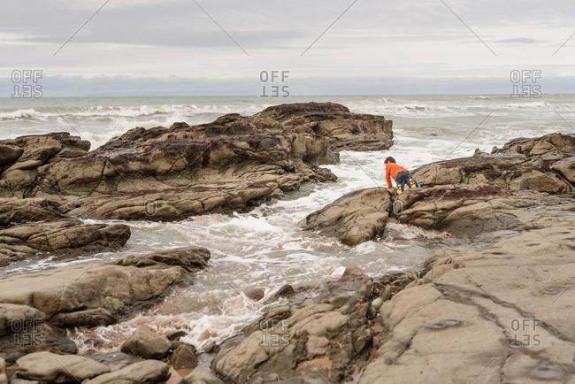 Young boy explores the rocky beach shore