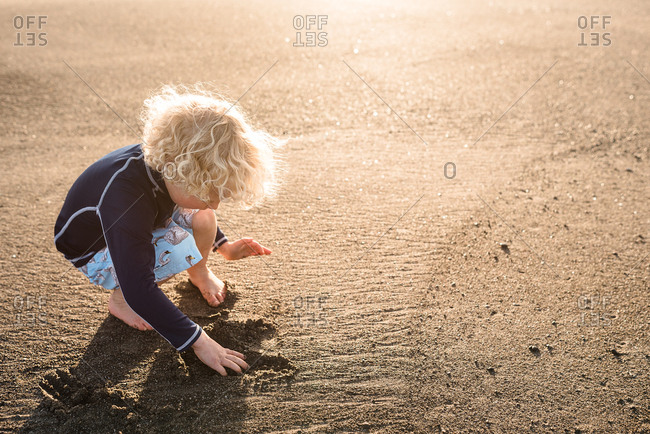 Young boy digging in sand