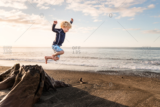 Boy jumps from tree stump at the beach