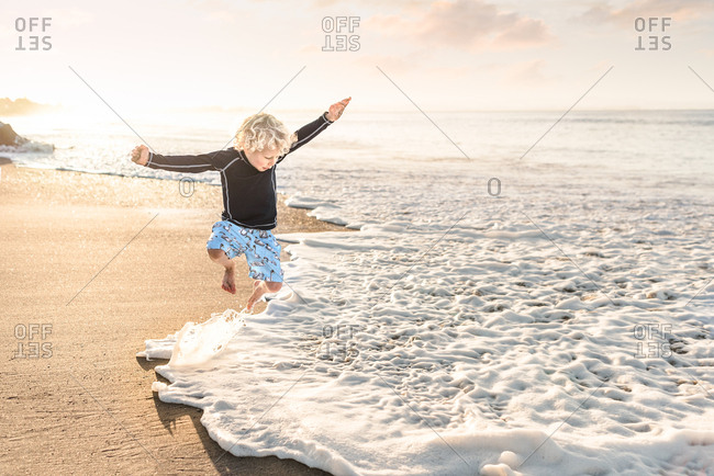 Young boy jumps above surf