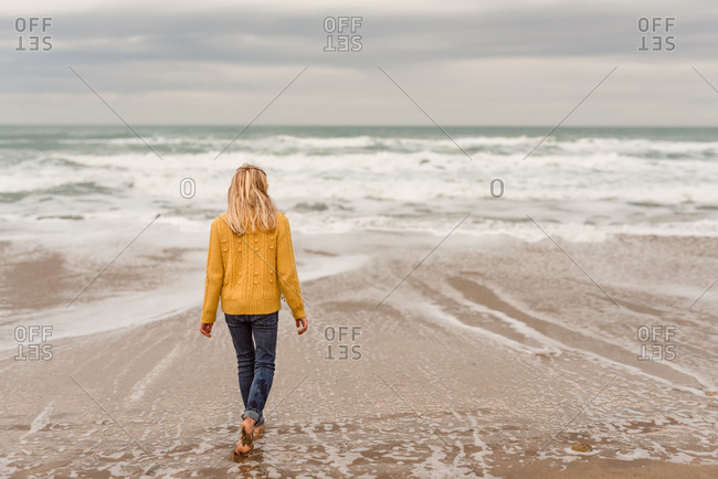 Girl walks barefoot into the surf