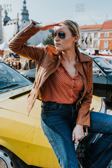 Blonde woman in late twenties sitting on yellow oldtimer car wearing retro seventies clothes style and aviator glasses