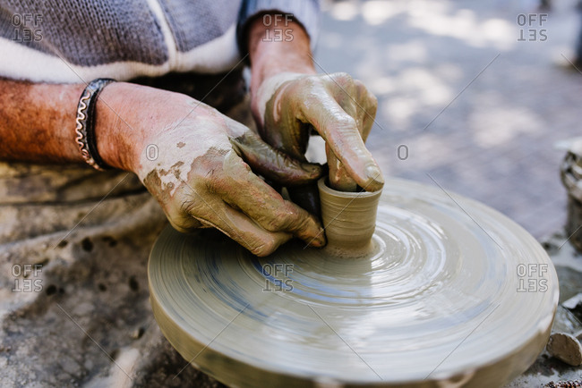 Hands sculpting clay on pottery wheel