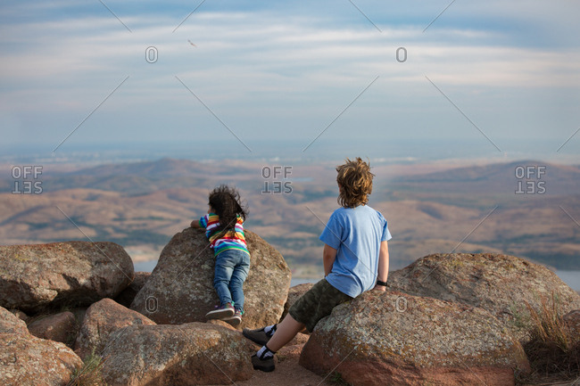 Boy and girl looking out at scenic view from mountaintop